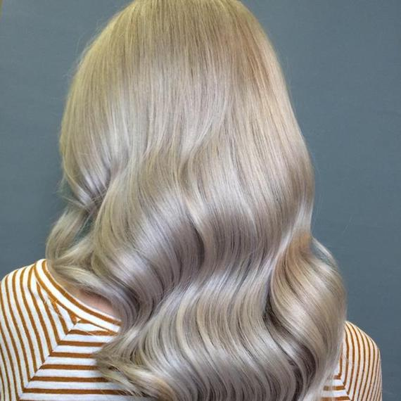 Photo of the back of a woman's head with long, wavy, blonde hair, glossed using Wella Professionals