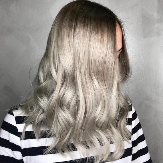 Side profile of woman with mid-length, wavy, silver hair, glossed using Wella Professionals