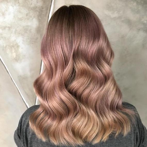 Photo of the back of a woman's head with shiny, tousled, rose gold hair, glossed using Wella Professionals