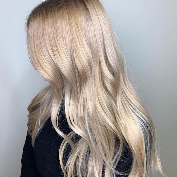 Side profile of woman with long, wavy, blonde hair, glossed using Wella Professionals