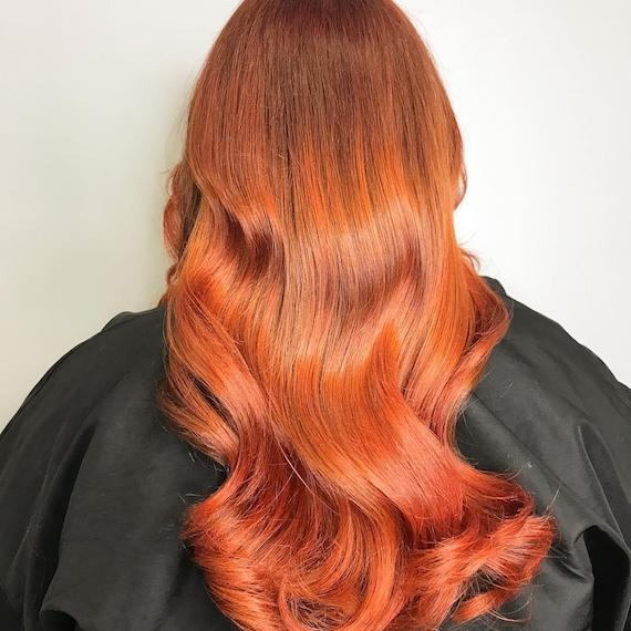 Photo of the back of a woman's head with copper, wavy hair, glossed using Wella Professionals