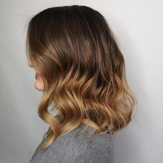 Side profile of woman with blonde balayage through brunette hair, glossed using Wella Professionals