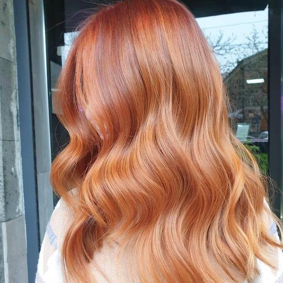 Side profile of woman with strawberry blonde glossy waves, created using Wella Professionals.
