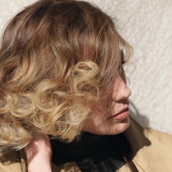 Kuva naisesta, jolla on lyhyet, aaltoilevat, vaaleat hiukset, luotu Wella Professionals -sovelluksella.