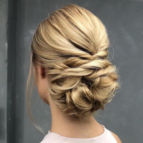 Kuva naisesta, jolla on vaaleat hiukset, muotoiltu matalalla chignonilla, luotu Wella Professionalsin avulla.