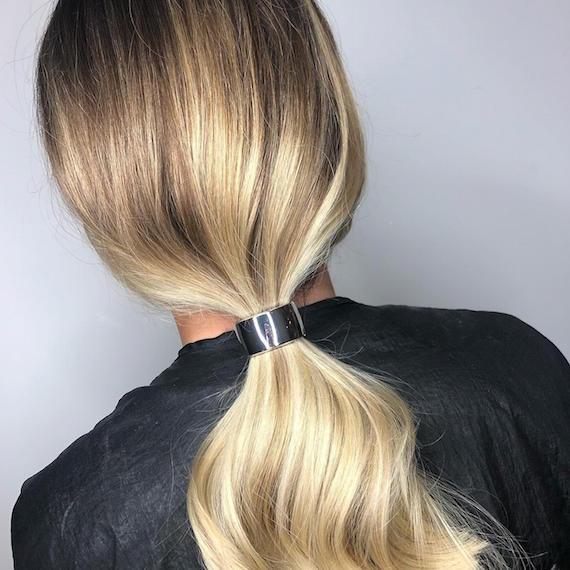 Kuva naisesta, jolla on vaaleat hiukset, muotoiltu matalalle ponille, luotu Wella Professionals -sovelluksella.