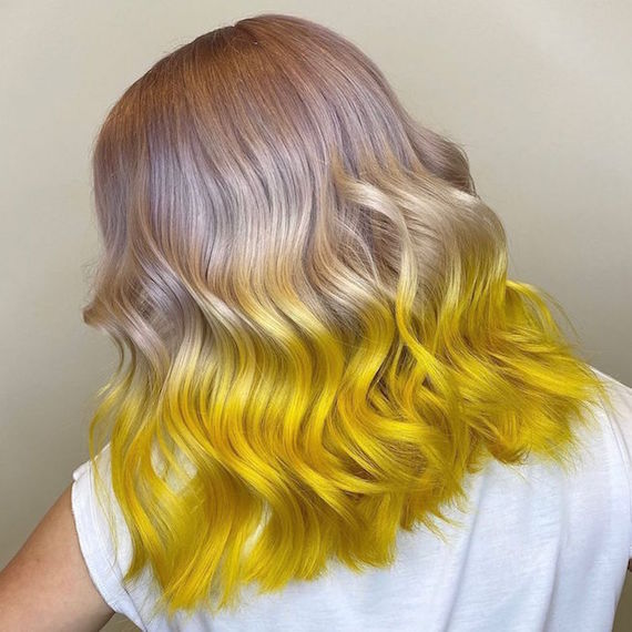 Back of woman's head with half and half hair color in violet blonde and neon yellow, created using Wella Professionals.