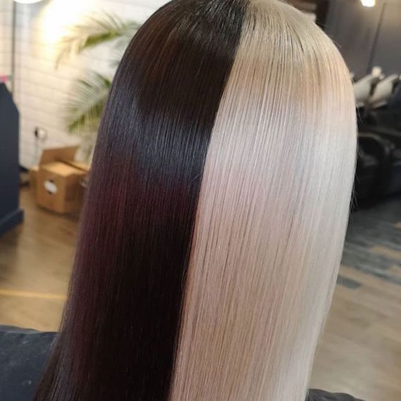 Back of woman's head with half and half hair color in ice blonde and black, created using Wella Professionals.