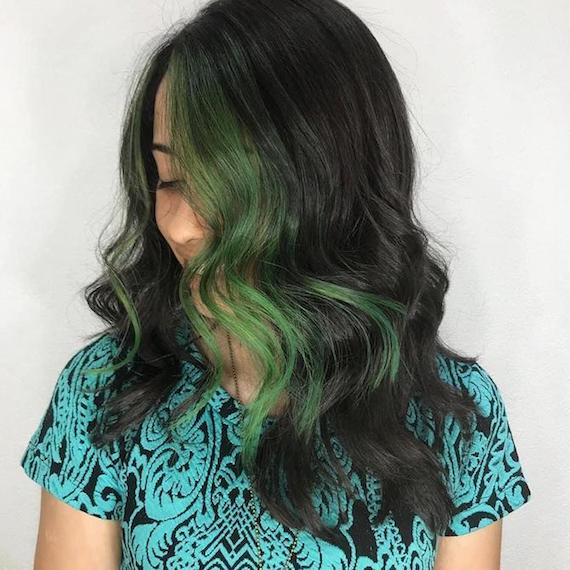 Woman with long, wavy, dark brunette hair featuring green streaks, created using Wella Professionals.