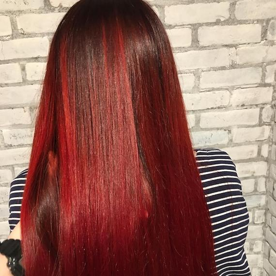 Back of woman's head with long, straight, red and black hair, created using Wella Professionals.