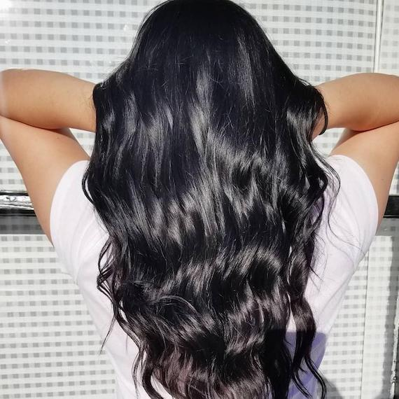 Back of woman's head with long, shiny, black, wavy hair, created using Wella Professionals.