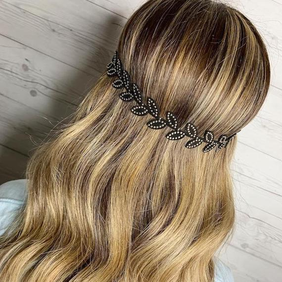 Back of woman's head showing long, wavy, blonde hair with a headband, created using Wella Professionals.