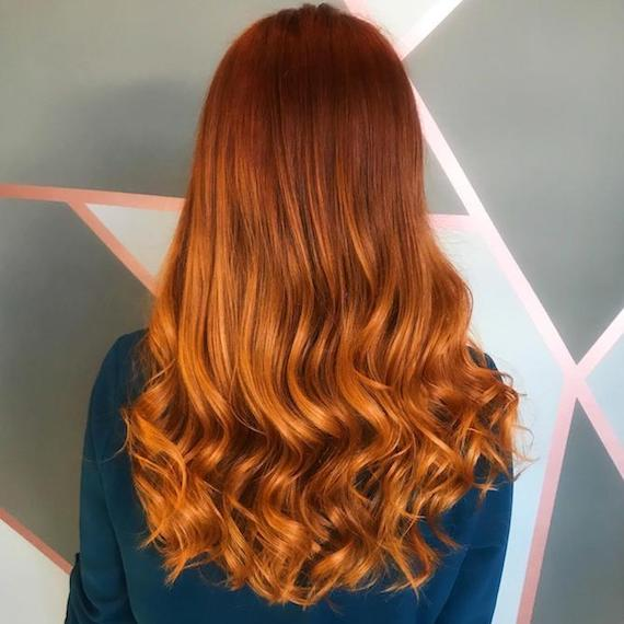Back of a woman's head showing long, wavy, pumpkin spice hair, created using Wella Professionals.