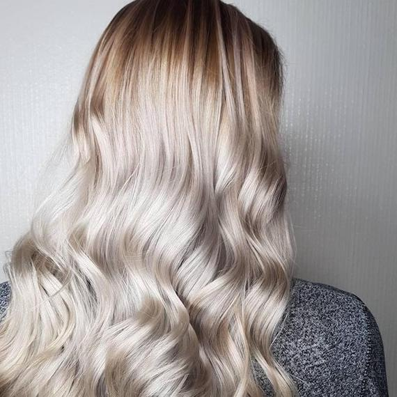 Back of a woman's head showing long, wavy, ice blonde hair, created using Wella Professionals.