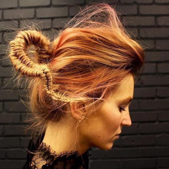 Side profile of woman with red hair teased into a tight fishtail braid, created using Wella Professionals.