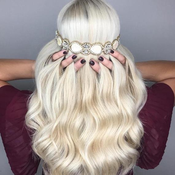 Back of a woman's head with long, wavy, blonde hair and Grecian headband, created using Wella Professionals.