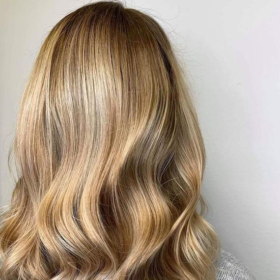 Back of woman's head with honey blonde babylights, created using Wella Professionals.