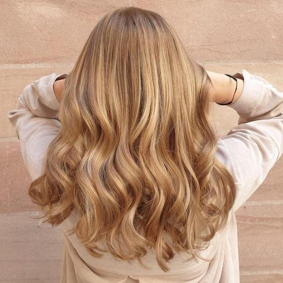 Back of woman's head with honey blonde foilyage, created using Wella Professionals.