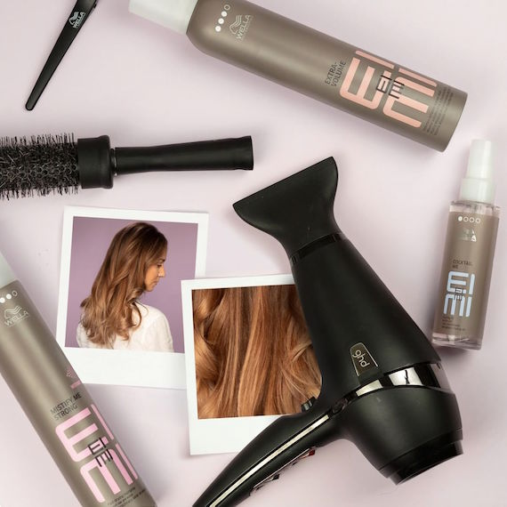 Flat lay of Wella Professionals EIMI products, hairbrush and hairdryer