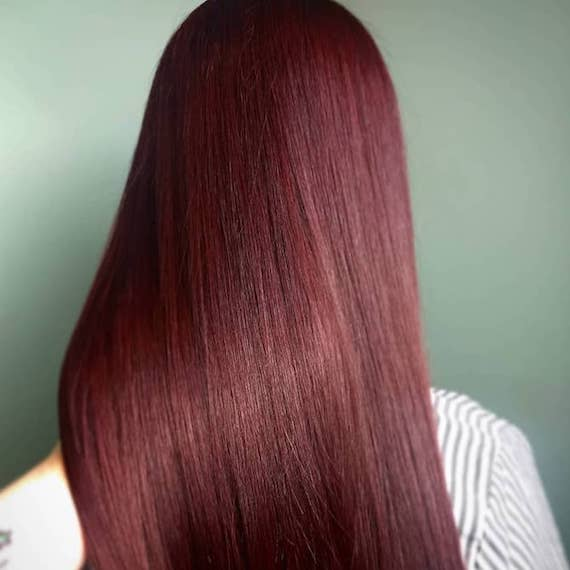Back of woman's head with long, straight, mahogany hair, created using Wella Professionals.