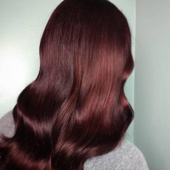 Back of woman's head with long, glossy, wavy, mahogany hair, created using Wella Professionals.