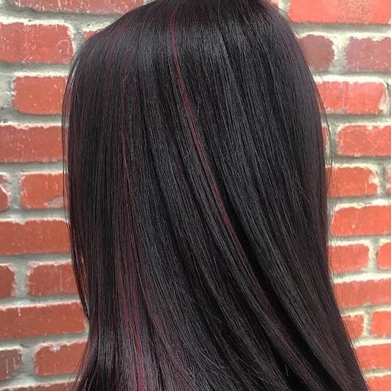 Side profile of woman with long, dark hair and mahogany red highlights, created using Wella Professionals