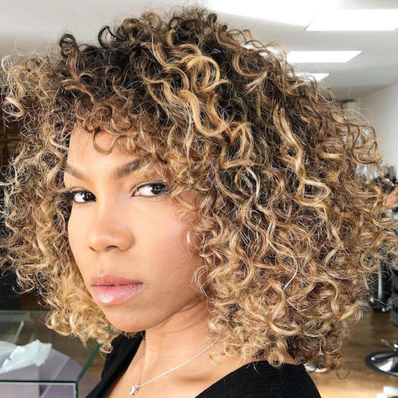 Photo of woman with curly hair and blonde highlights, created using Wella Professionals.