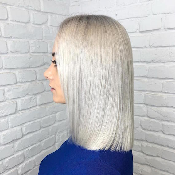 Side profile of woman with ice blonde lob, created using Wella Professionals.