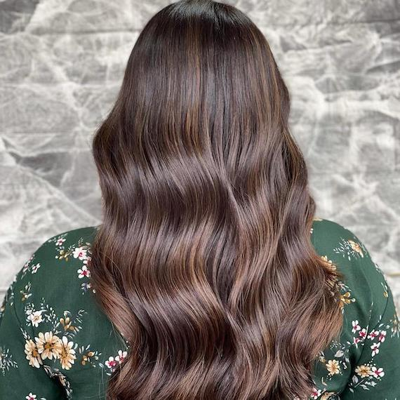 Back of woman's head with long, wavy, medium mocha brown hair, created using Wella Professionals.
