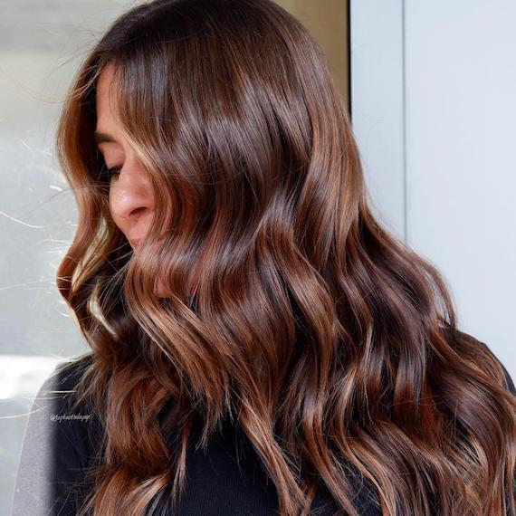 Side profile of woman with tousled, chestnut mocha brown hair, created using Wella Professionals.