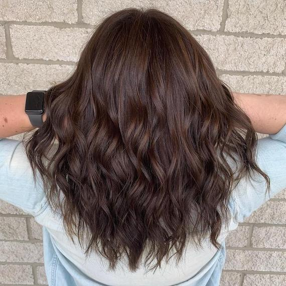 Back of woman's head with tousled, dark mocha brown hair, created using Wella Professionals.