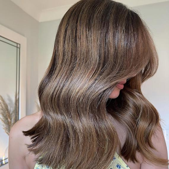 Side profile of woman with brown hair and chunky bronde highlights, created using Wella Professionals.
