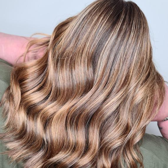 Back of woman's head with wavy, mocha blonde, highlighted hair, created using Wella Professionals.