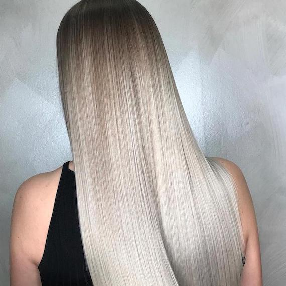 Back of woman's head with long, straight, silky, silver ombre hair, created using Wella Professionals.