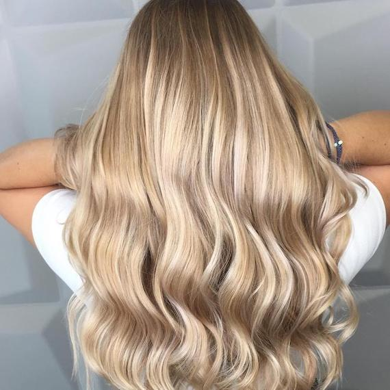 Back of woman's head with long, wavy blonde hair and balayage, created using Wella Professionals.