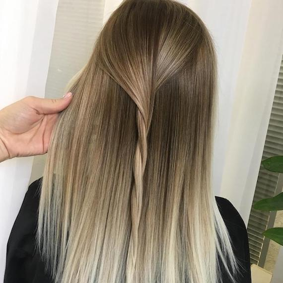 Back of woman's head with long, straight, brown to blonde ombre hair, created using Wella Professionals.