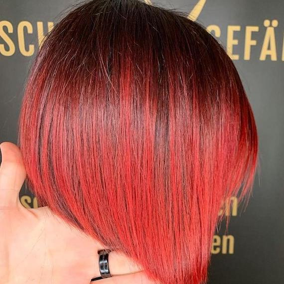 Side profile of woman with red ombre hair cut into a bob, created using Wella Professionals.