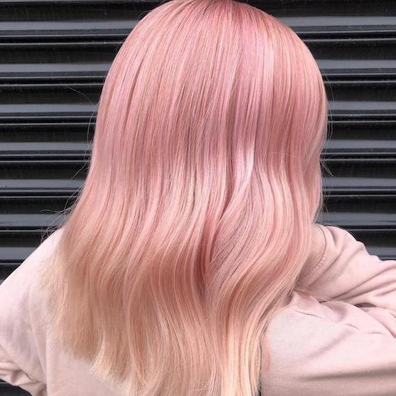 Back of woman's head with mid-length, pink ombre hair, created using Wella Professionals.