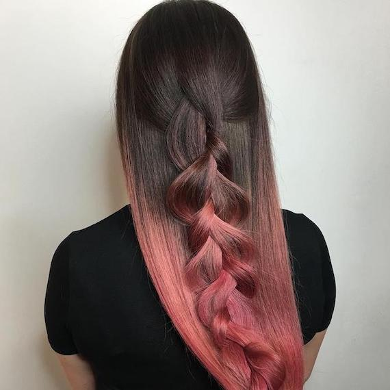 Back of woman's head with long, straight, black and pink ombre hair, created using Wella Professionals.