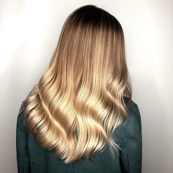 Back of woman's head with full, blonde balayage, created using Wella Professionals.