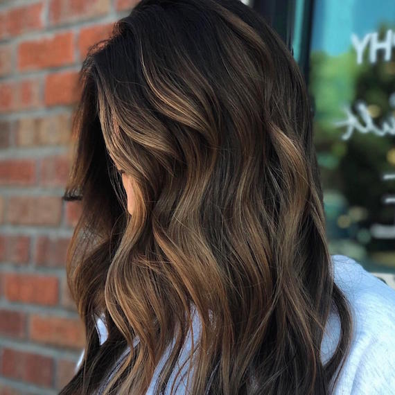 Side profile of woman with partial balayage through long, brown hair, created using Wella Professionals.