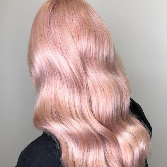 Back of woman's head with long, wavy, pastel rose gold hair, created using Wella Professionals.