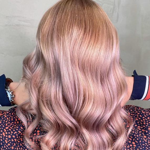 Back of woman's head with long, wavy, pastel pink and blonde hair, created using Wella Professionals.