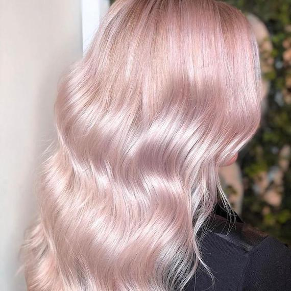 Back of woman's head with long, wavy, pastel pink hair, created using Wella Professionals.