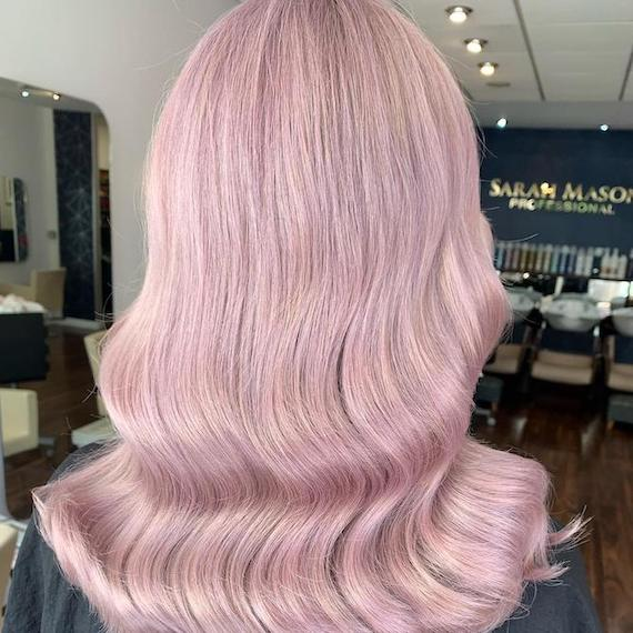 Back of woman's head with long, wavy, purple-pink hair, created using Wella Professionals.