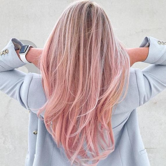 Back of woman's head with long, straight, pink blonde ombre hair, created using Wella Professionals.