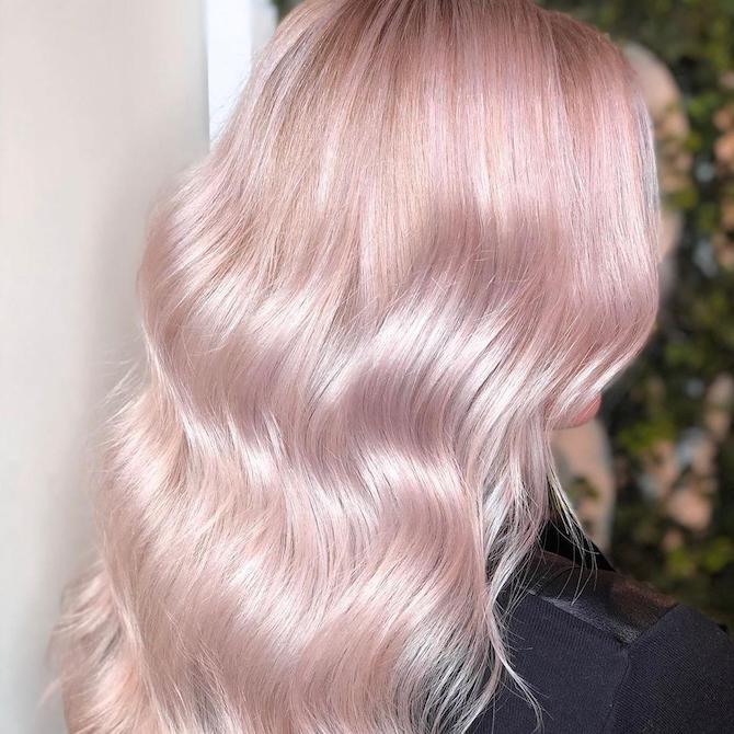 Back of woman's head with long, wavy, pink platinum hair, created using Wella Professionals.
