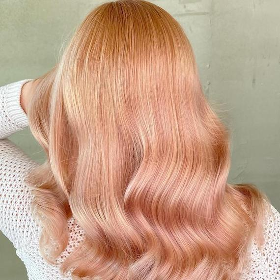 Back of woman's head with wavy, rose gold hair, created using Wella Professionals.