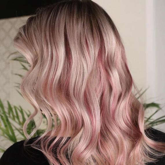 Back of woman's head with pink blonde hair and dark roots, created using Wella Professionals.