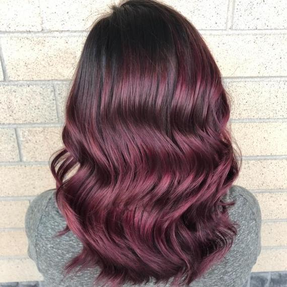 Back of woman's head with long, wavy, plum hair color, created using Wella Professionals.